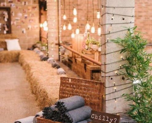 We love the rustic meets industrial decor vibe. Bales of hay, exposed brick and hanging Edison bulbs. Blankets in a basket favors make loving winter wedding ideas.