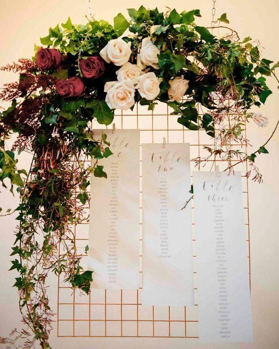 Una reja adornada con flores y hiedra se transforma en un seating chart.