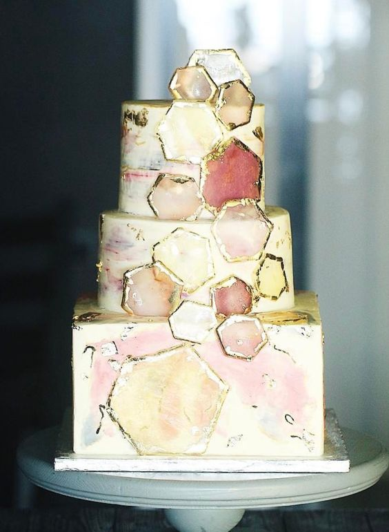 Square and round wedding cake with hexagonal art.