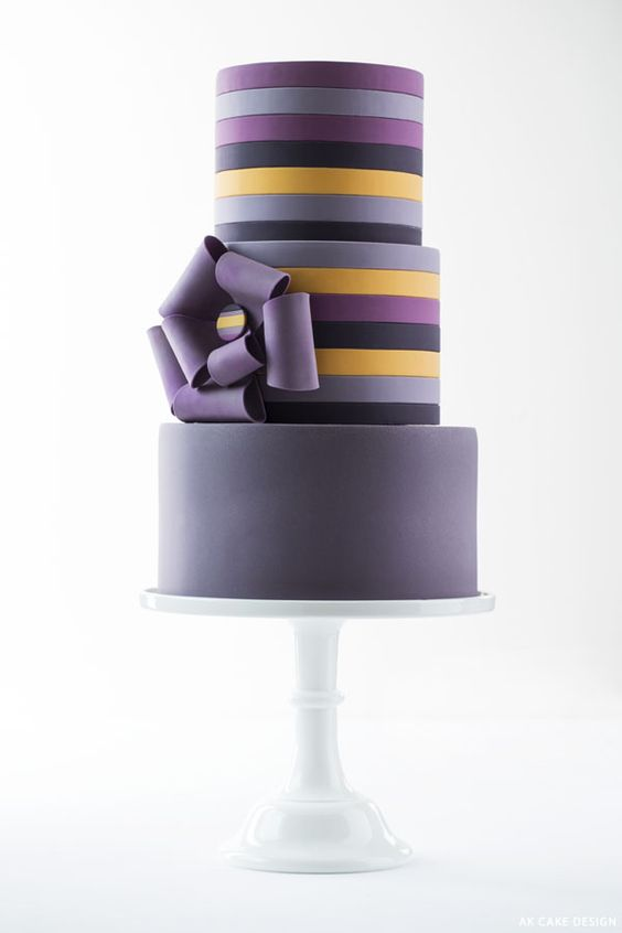 Forego the traditional white wedding cake for a swoon-worthy and unique wedding cake design in purple, plum and yellow stripes. Photography Lara Ferroni.