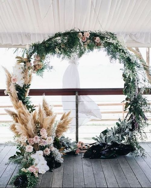 Bring a bit of frost to your winter beach wedding. Add dusty millers to the circular wedding ceremony arch background. Photo: Jasmine lee photography.