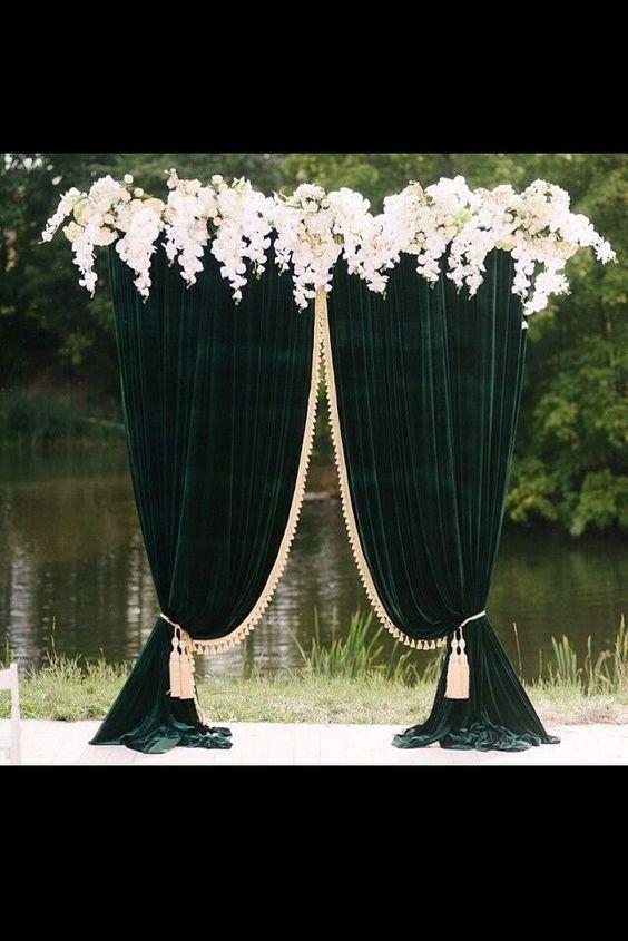 Altar de boda de terciopelo verde cubierto con borlas de oro y borde de orquídeas blancas de unique pastiche events.
