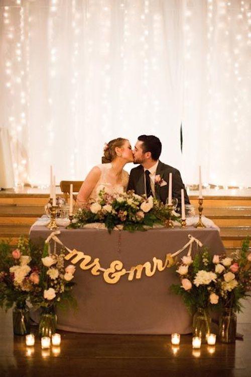 Ambienta la mesa de los novios con románticos arreglos florales, velas y un backdrop que refleje la luz y ¡que se besen!