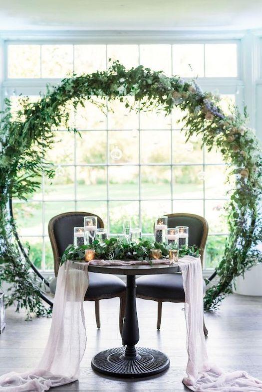 Infaltables en la ambientación de bodas de hoy en día, los arcos florales gigantes engalanan el background de la mesa de la feliz pareja. Camino de mesa de chiffon por rocknevents.