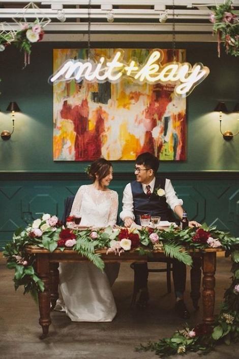 Los letreros de boda de neón son hermosos, y me fascina su variedad de usos. Una ambientación de mesas de novios espectacular. Incorpora ramas de helecho totalmente en tendencia este año en un entorno moderno e industrial.