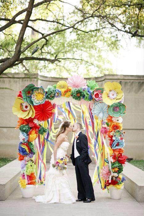 Arco de ceremonia para una boda Mexicana. Un par de cubetas, un arco, flores gigantes en colores vivos donde predominen el verde, amarillo y rojo y listones de raso.
