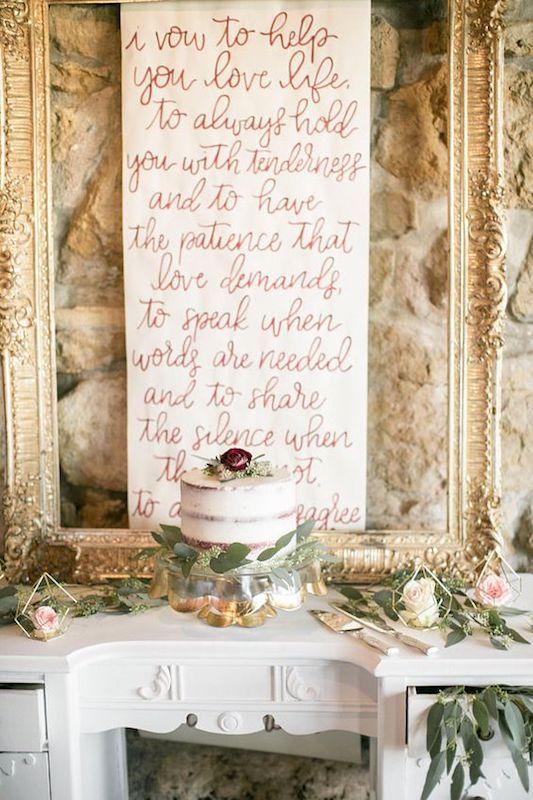 Los votos matrimoniales escritos en el backdrop de la tarta de bodas. Hecho a mano en caligrafía.