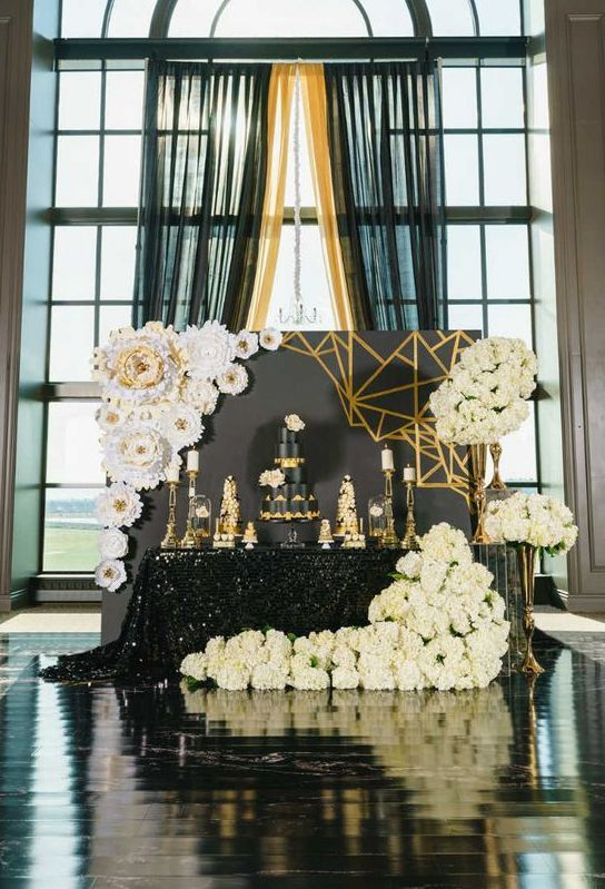 Backdrop de tarta nupcial para una boda inspirada en La La Land. Holywood glam con flores de papel y fondo en negro y dorado.