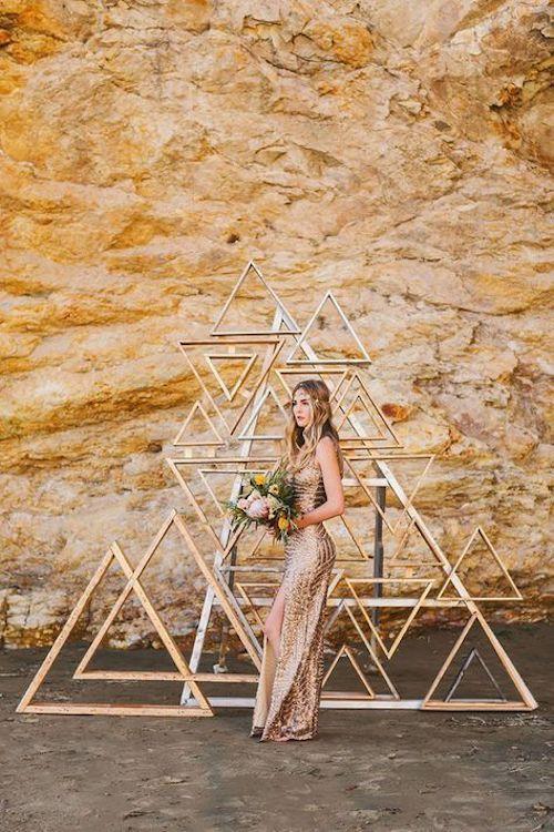 Original al máximo, los backdrops para boda hechos con figuras geométricas están en tendencia. Triángulos de madera en dorado para una boda glam o industrial.