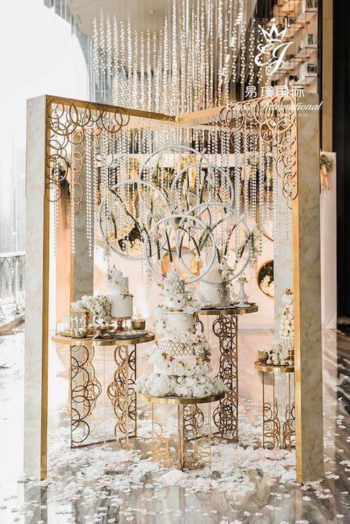 ¿Qué opinas de estos backdrops para bodas? Cortan la respiración, ¿no? Círculos y tiras de perlas colgantes en blanco y dorado enmarcado por puertas decoradas.