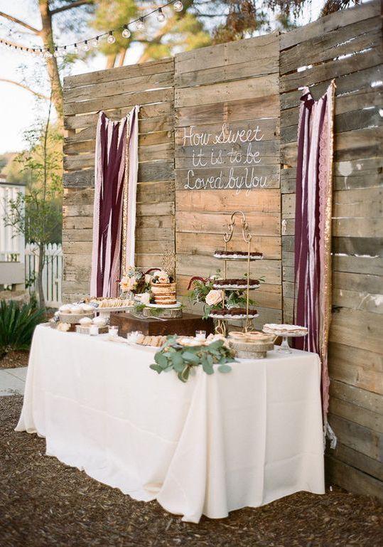 Boda rústica boho en California con un fondo de mesa de dulces hecha de cajones de madera y cintas en los colores de la misma. Suma una frase de amor.