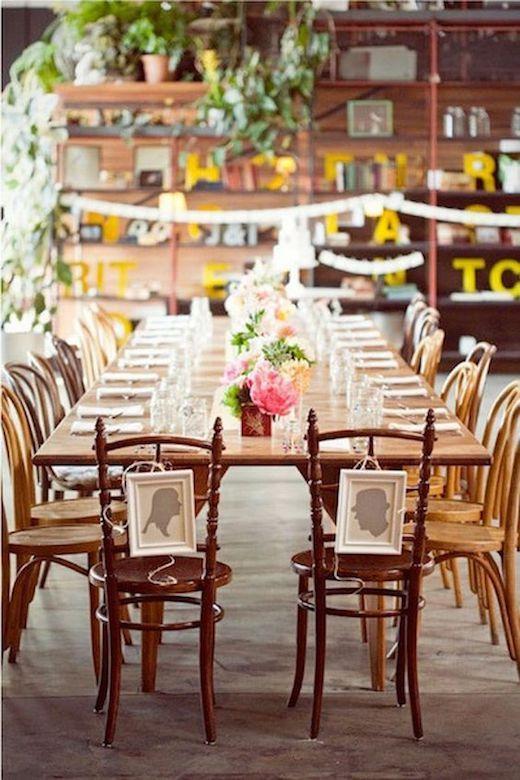 Los novios en la cabecera de la mesa principal y para que nadie se siente en sus sillas, un par de cuadros super originales.