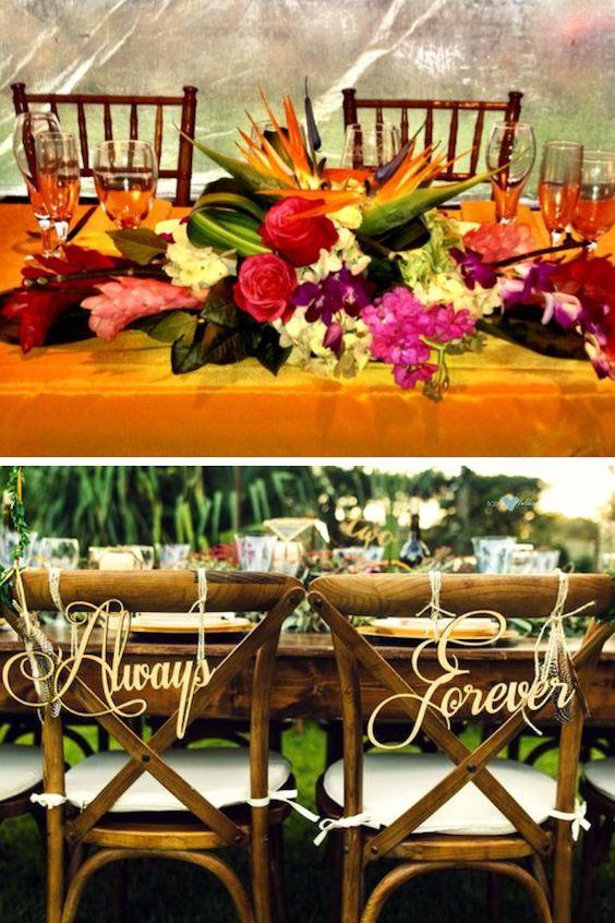 Centro de mesa tropical para la mesa principal de esta boda caribeña y sillas de caña con carteles. Christian david photo.