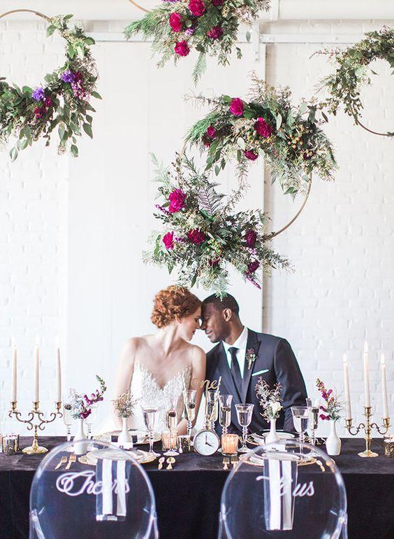 Nadie dijo que un telón de fondo tiene que ser cuadrado. Estas coronas con flores suspendidas presentan una perspectiva diferente en backdrops para bodas y llenan sin abrumar un espacio en blanco.