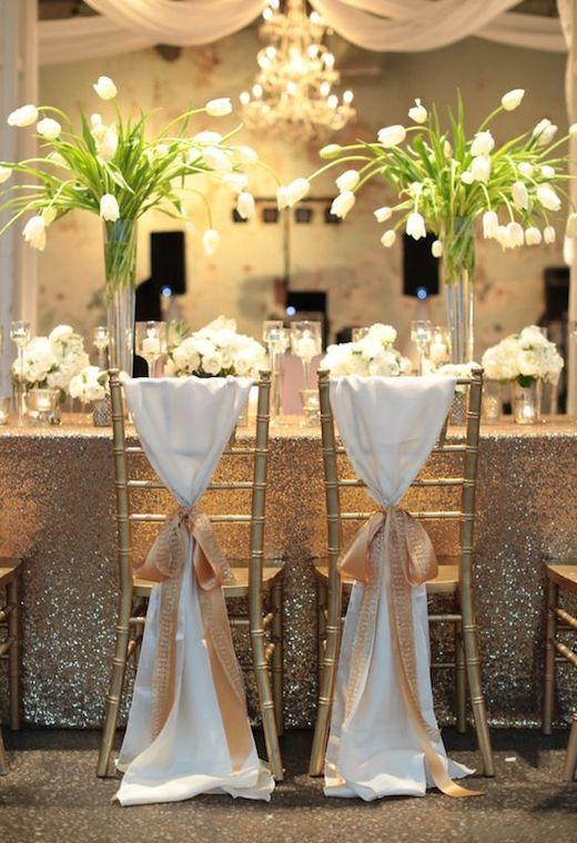 Decoración de banquete de bodas con seda y pailletes. Dos centros de mesa altos con tulipanes blancos flanquean el lugar para los novios.