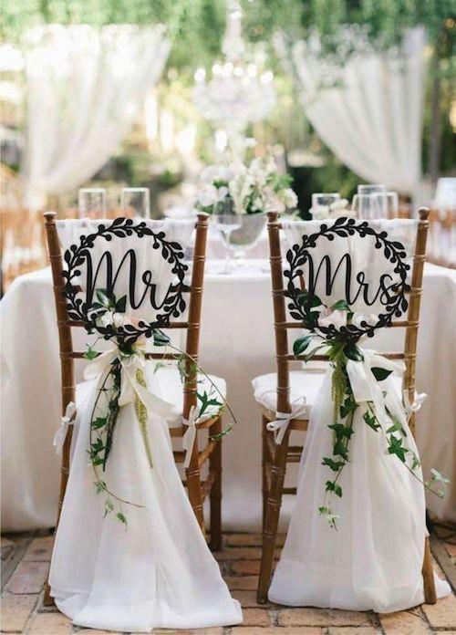 Una solución elegante para la decoración de las sillas de los novios. Cartel de madera bordeado de laureles que se adapta a todo estilo de celebración.