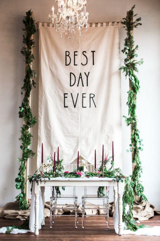 Idea de backdrop para la mesa de novios. Una bandera gigante con guirnaldas y una frase de amor. La mesa es sencilla pero con muy lindos detalles de velas y flores.