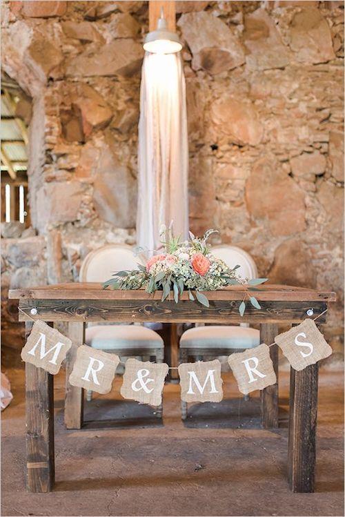 Simpatiquísima mesa de novios estilo rústico boho chic. Me encanta el detalle del velo que cuelga en la pared detrás de la mesa.