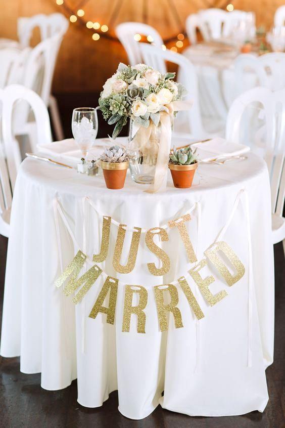 Detalles para ambientar la mesa de la flamante pareja. Dos macetas con suculentas, flores y un cartelito de recién casados.