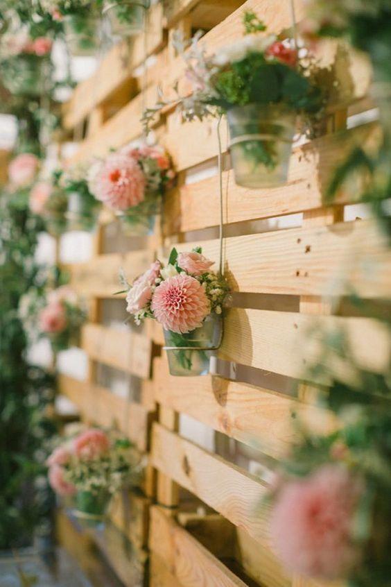 Un par de palets de madera se transforman en un romántico backdrop para boda en jardín.