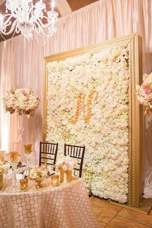 Lujoso telón de fondo floral para la mesa de los novios.