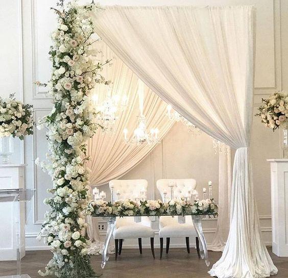 Usar dos telones de fondo para bodas no es novedad. Eleva el look de la mesa de los novios agregando una columna cubierta de flores y una lámpara tipo araña.