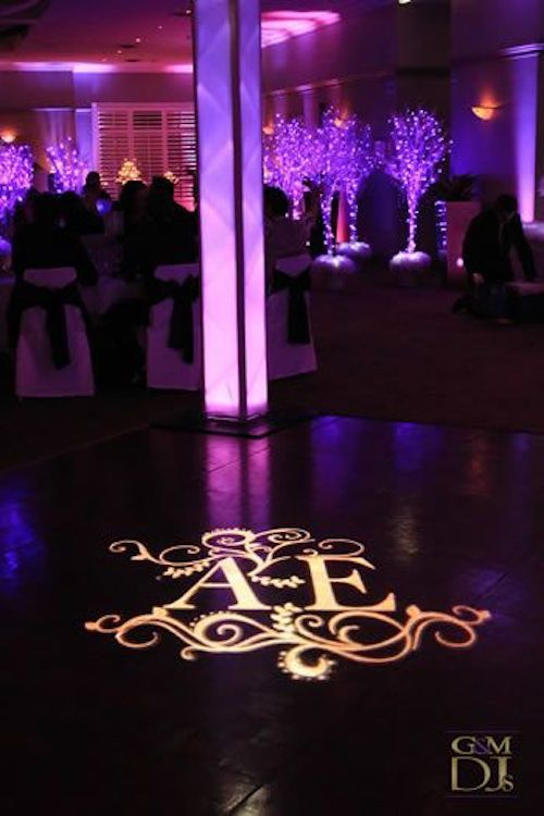 Want to truly impress your guests? Project a monogram on the dance floor. Uplights add a pop of color to the walls. Loving the purple beams and lighted tree centerpieces by GandM DJs.